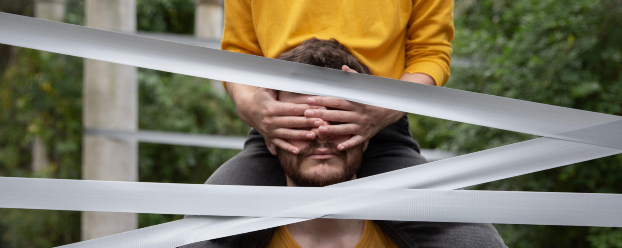 Man with a person on his shoulders, covering his eyes with their hands and gaffer tape across the screen.