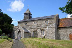 A grey stone church on a summer day