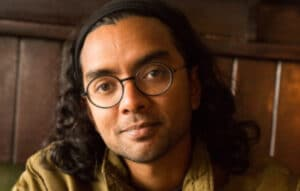 Poet Arji, close up of a mans face with round black rimmed glasses, long dark hair
