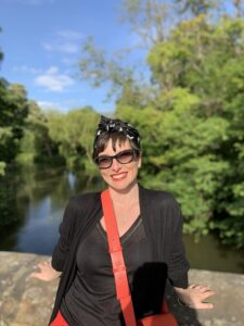 New staff member for Applause, Georgette Purdey, Lady with short dark hair standing in front of a river with some trees.