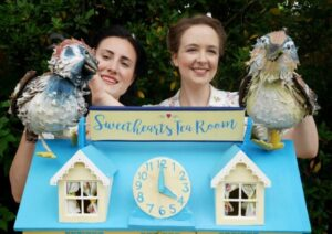bird puppets, two female actors and a large dolls house outdoors