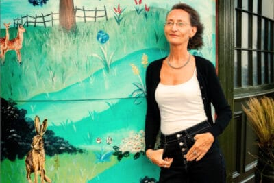 Woman standing in front of mural in jeans and white t shirt.