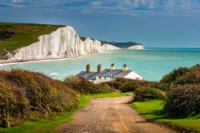 View of chalk cliffs, sea and cottages