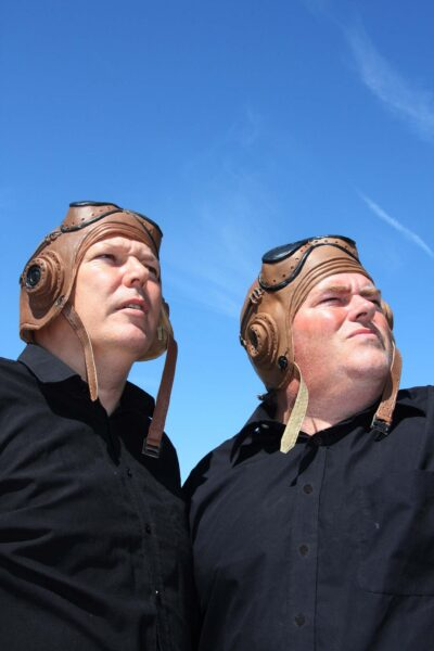 two actors wearing old flying helmets look to the sky