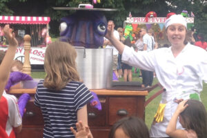Woman and a large Octopus puppet in a saucepan with children watching
