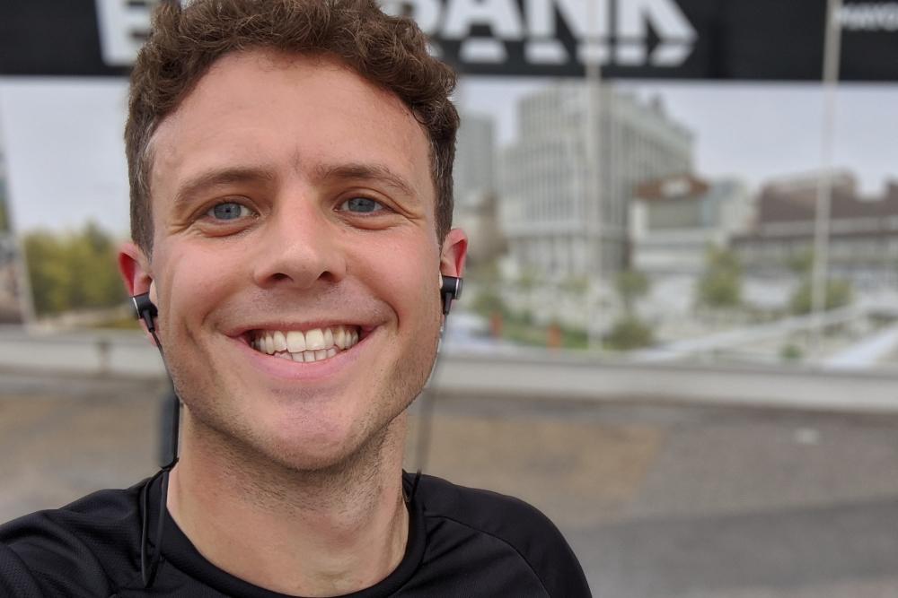 Image of Smiling man outside a billboard
