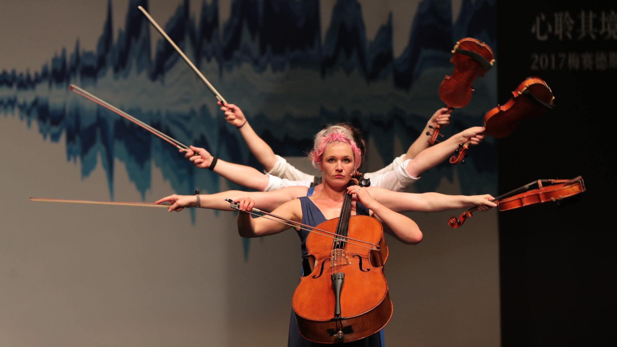 Female performer with instruments and many arms behind her
