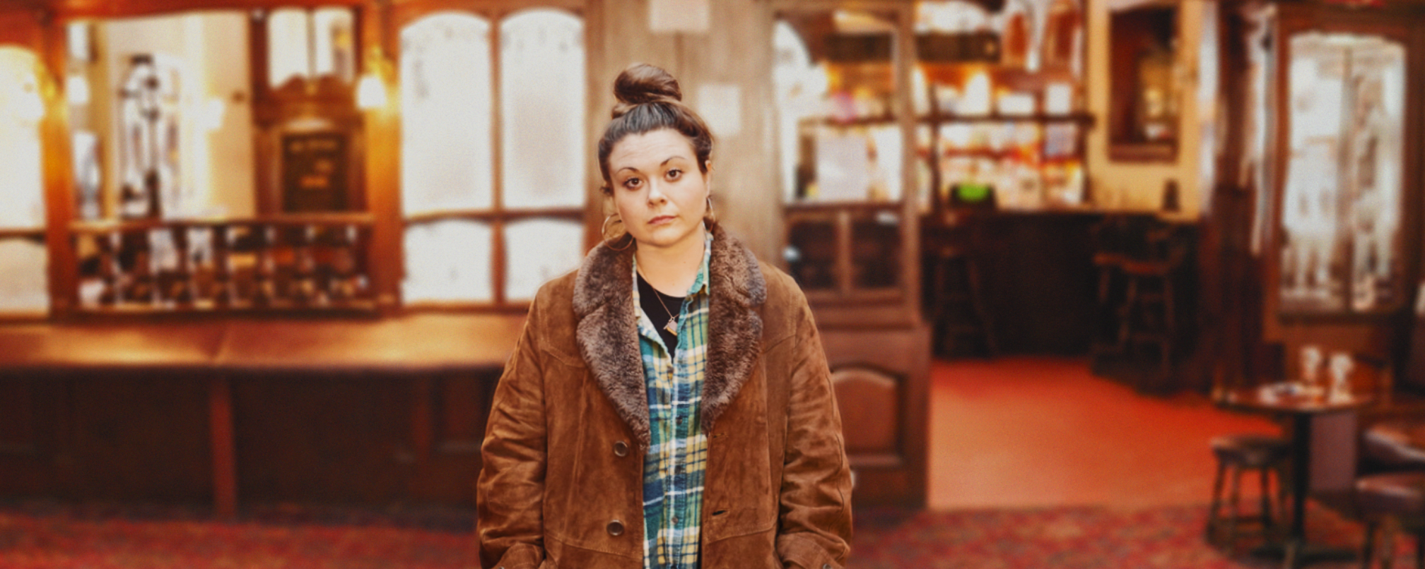 Woman in brown coat standing in the middle of an empty Pub