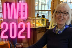 Woman sat in a bar with larger pink letters saying IWD 2021