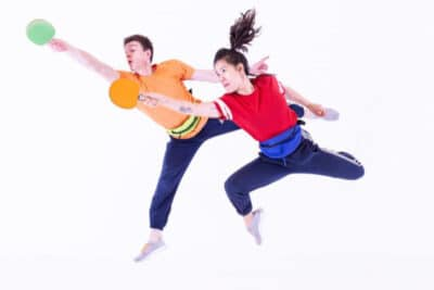 Two people jumping in mid air with ping pong bats