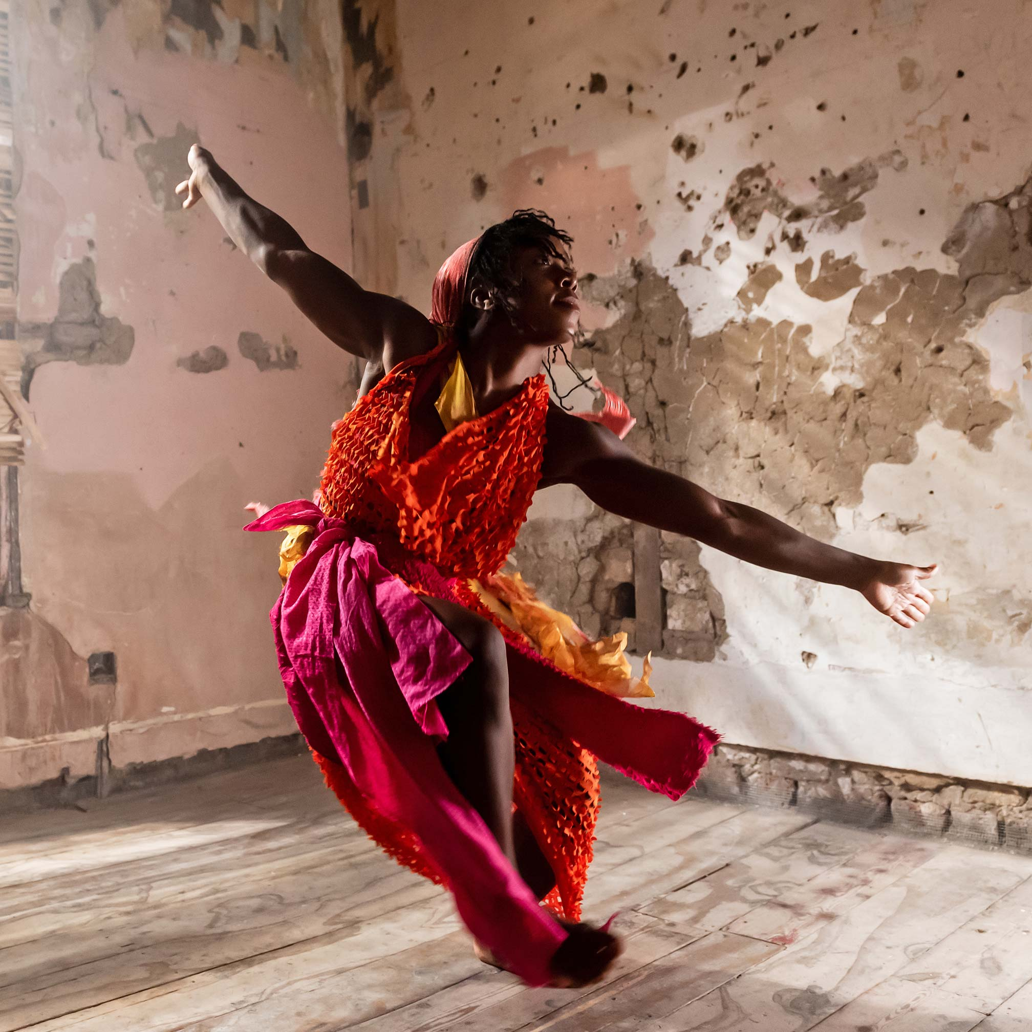 Asian dance artist in an empty building wearing pink and red
