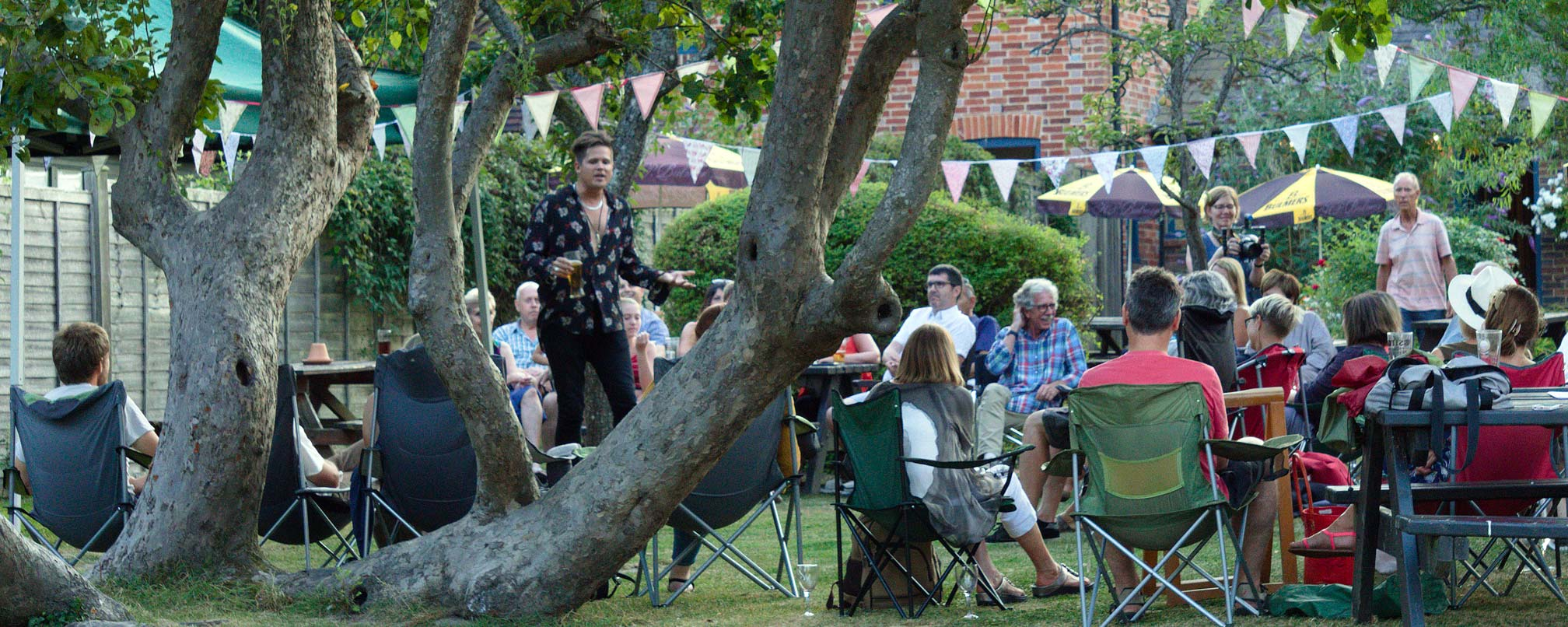 Performer in a pub garden with audience in the summertime