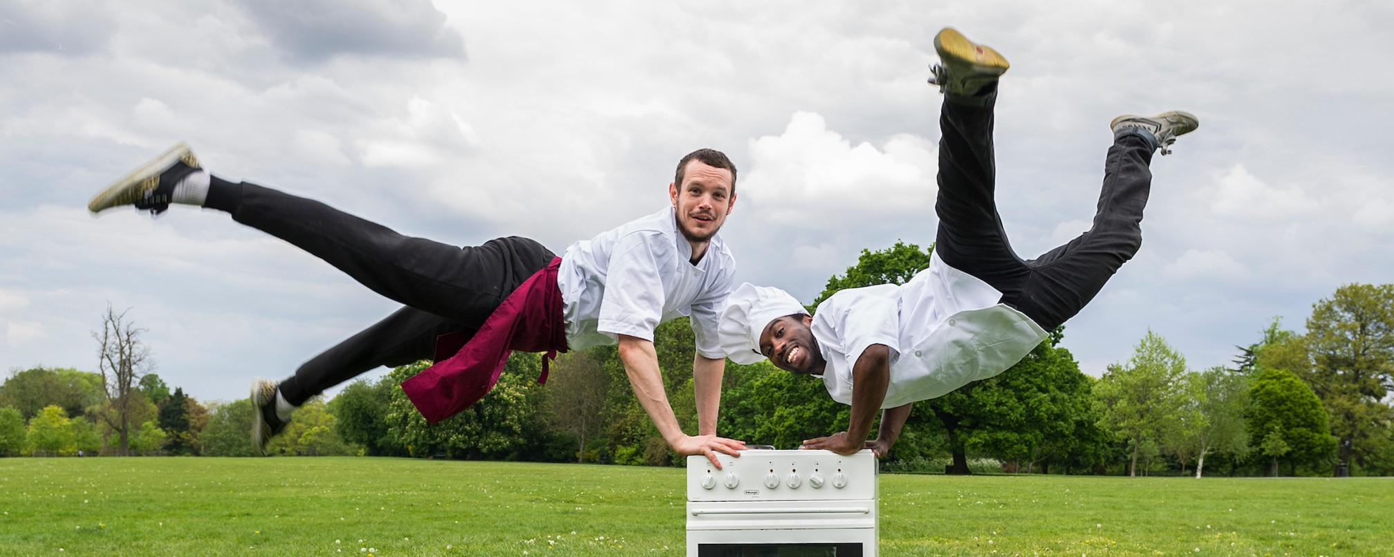 Two mean leaping in the air in chef's attire leaning on a cooker