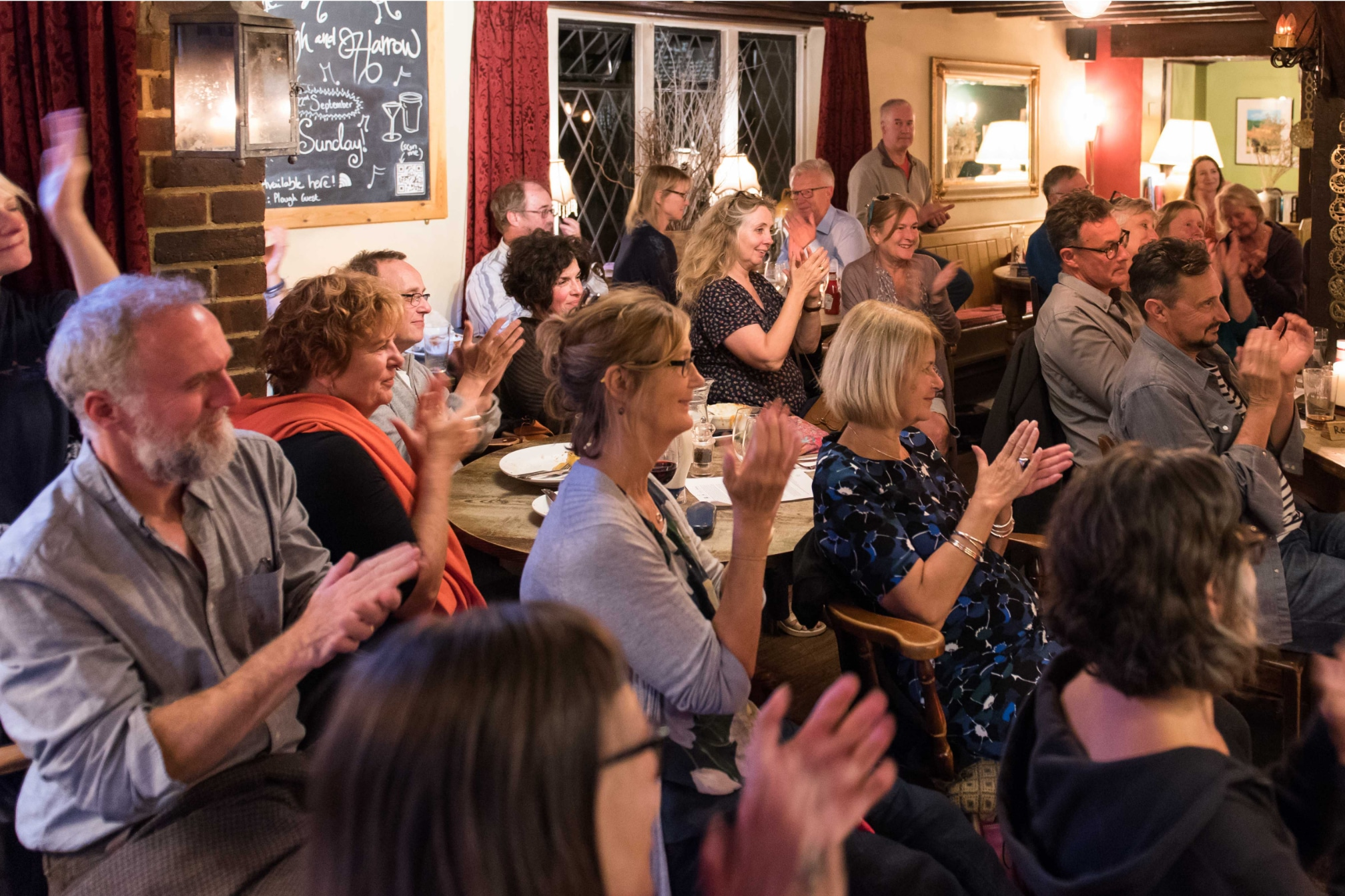 People in a pub applauding
