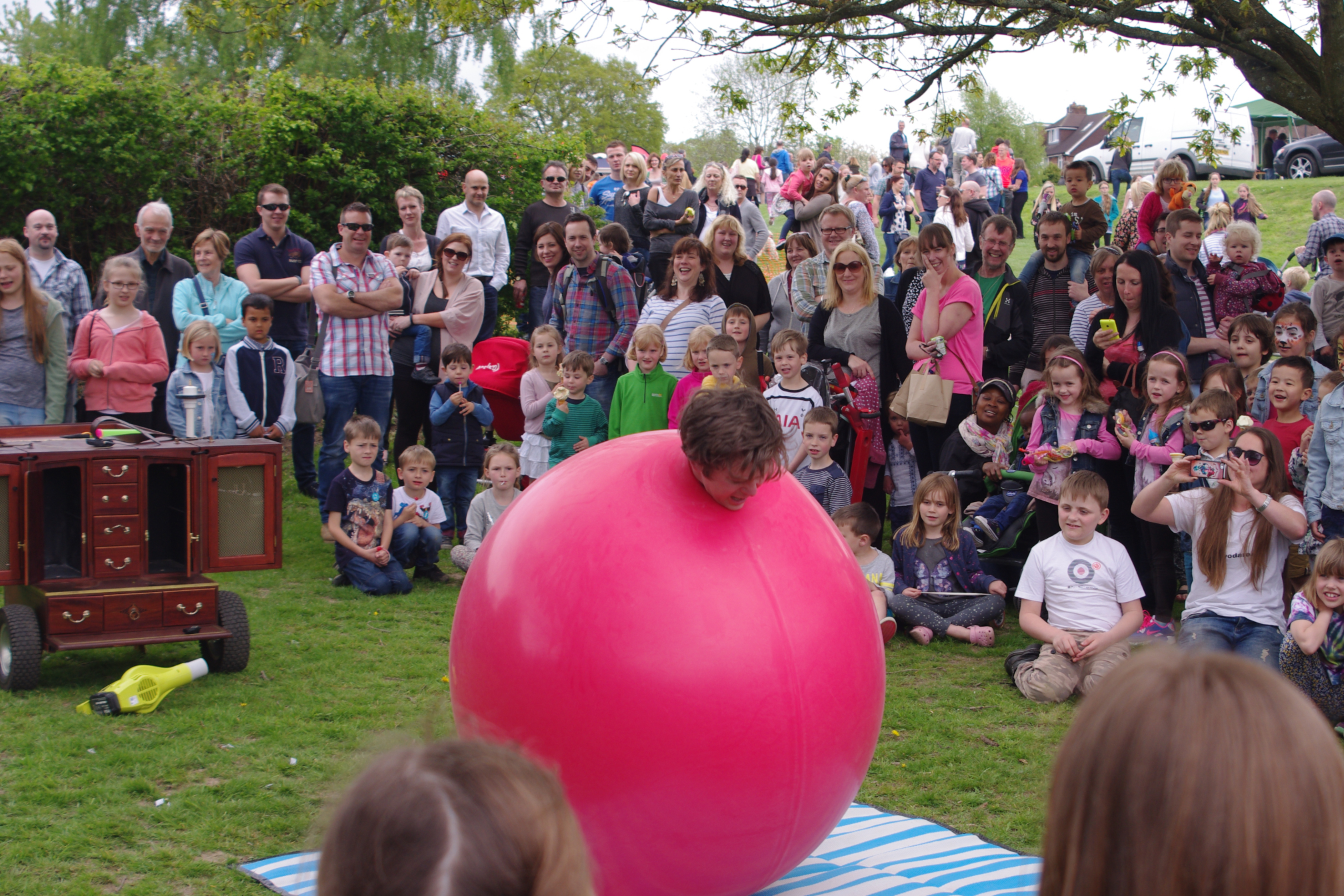 Crowd watching an artists emerge from a giant balloon
