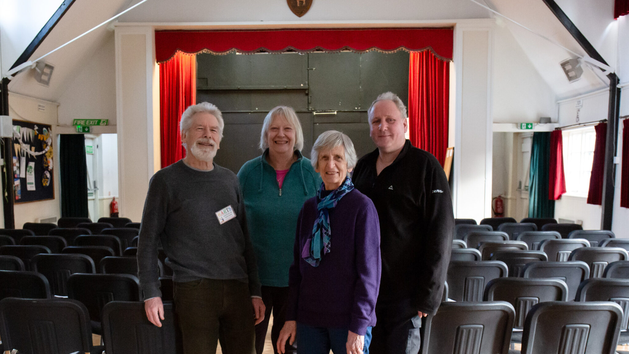 Four people n a line in front of a village hall stage