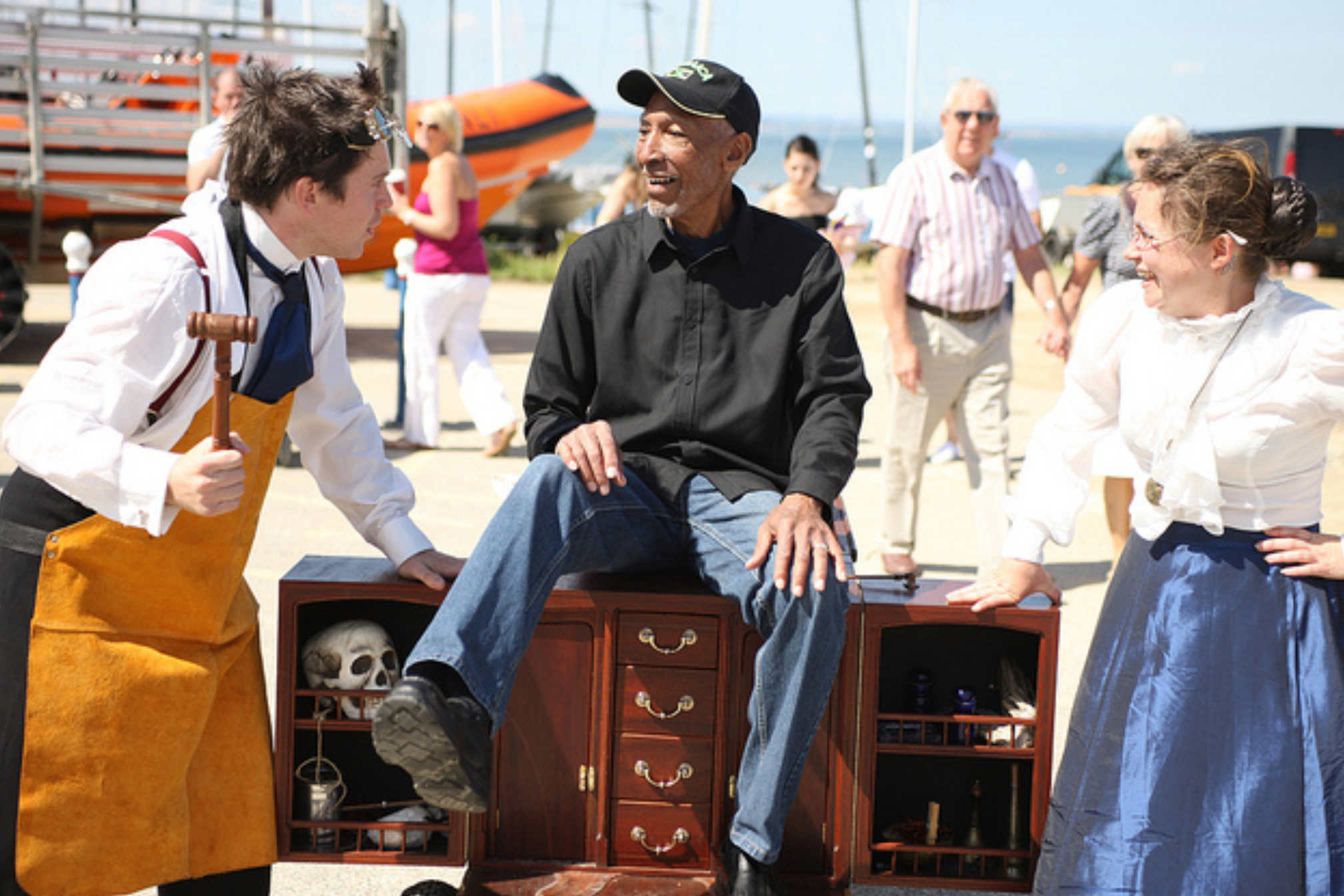 Man sat on sideboard with two performers in old victorian style dress