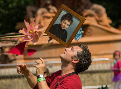 juggler balances a framed portrait on his nose