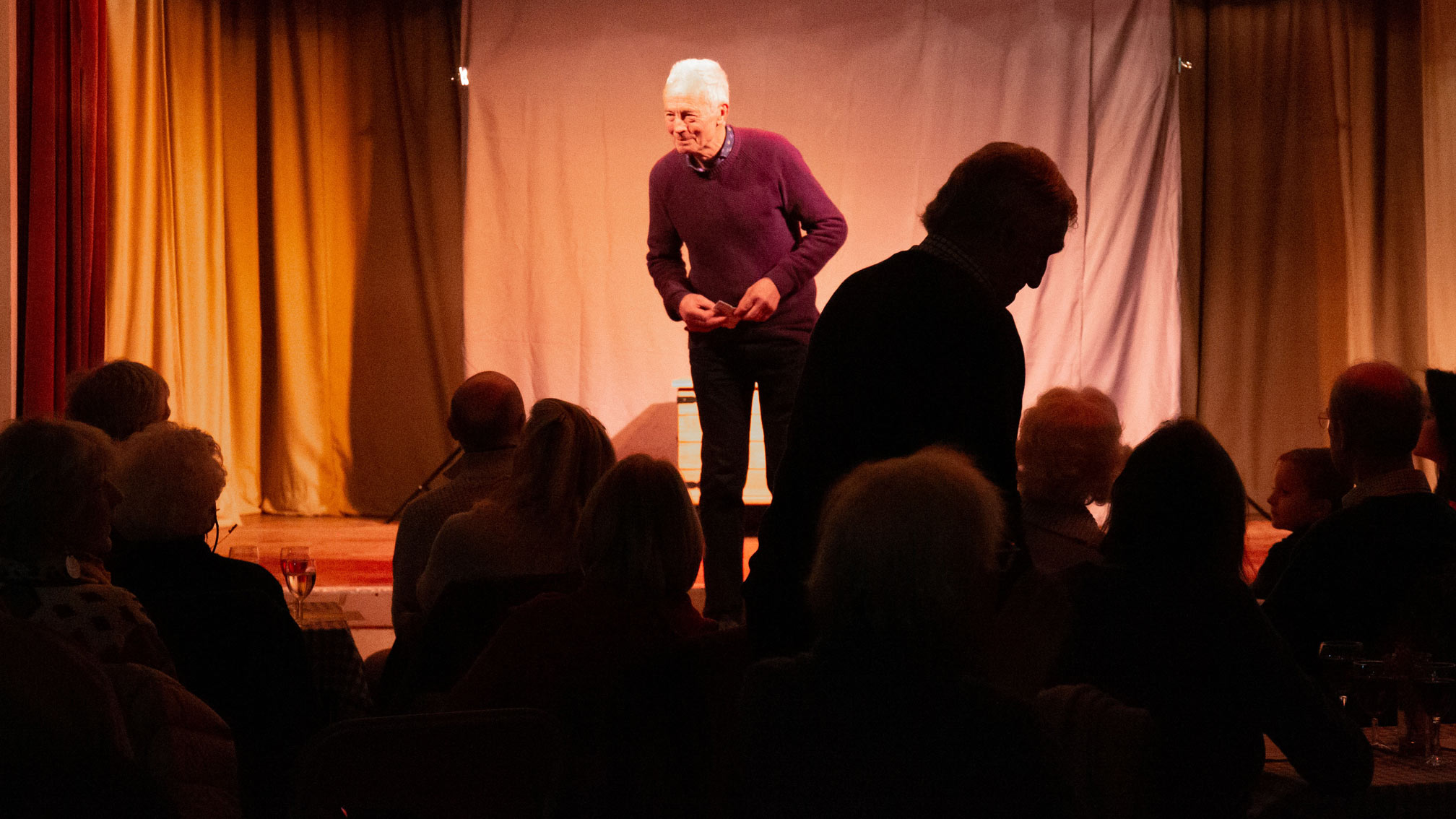 A grey haired man on stage introducing an act